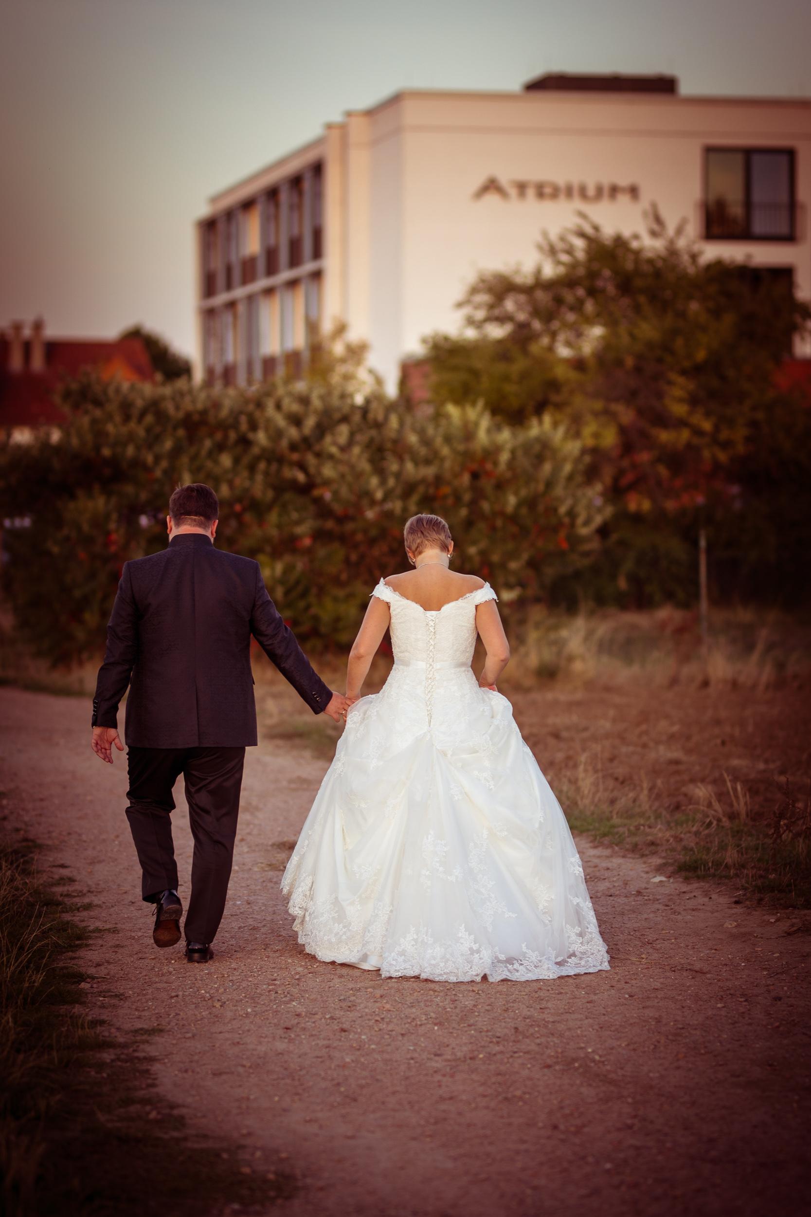 Hochzeitspaar auf Schotterweg vor Atrium Hotel Mainz